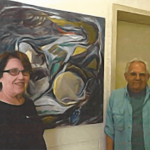 Two artists next to a piece of artwork